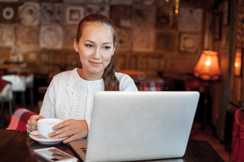 Yong woman a work at laptop in cafe royalty free stock photos