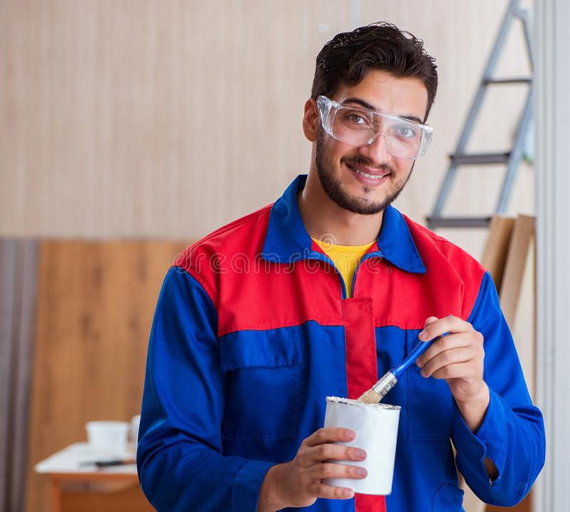 Yooung repairman carpenter working with paint painting stock image