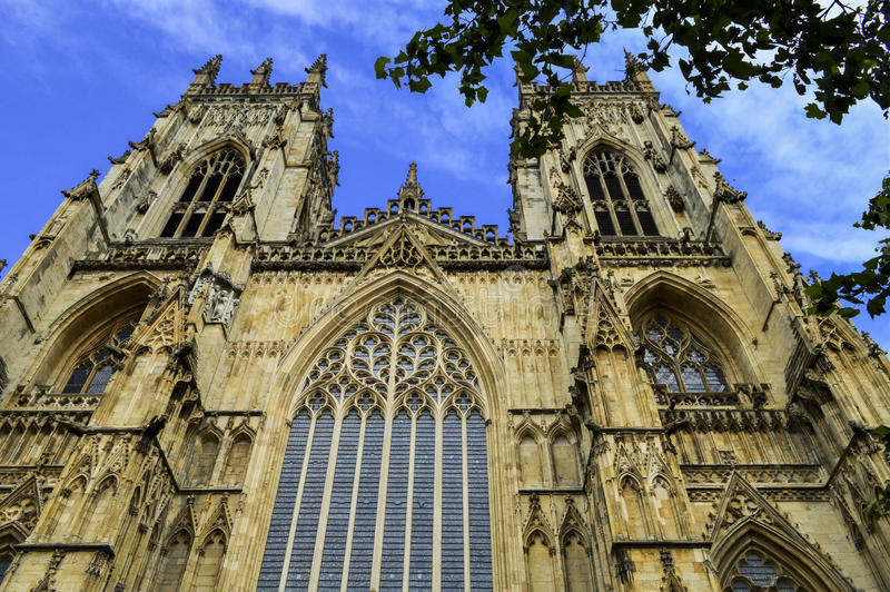 York Cathedral and Blue Sky, England. Ancient York Cathedral Tower, Cloudy Blue Sky, sandstone and windows in England royalty free stock photo