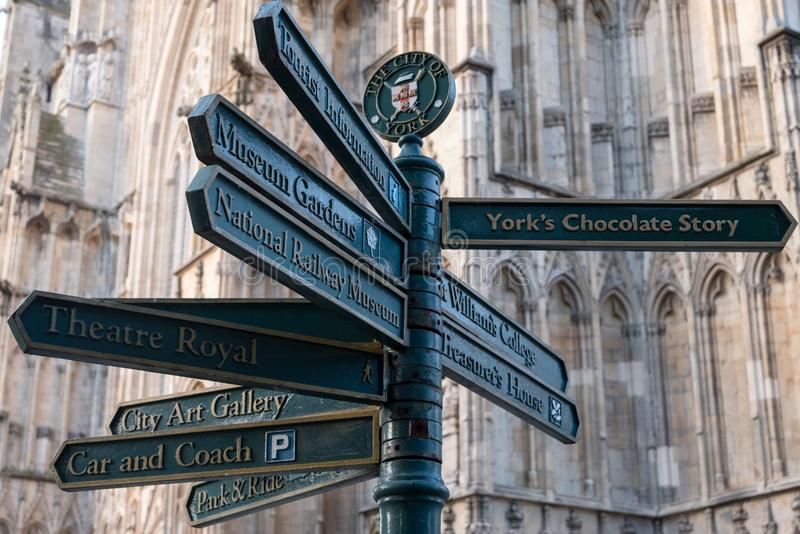York Minster in background. In foreground street sign giving directions to various places of interest to tourists in York. royalty free stock image