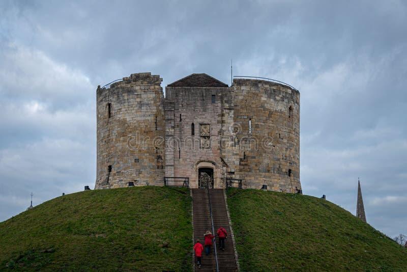 YORK, INGLATERRA, EL 12 DE DICIEMBRE DE 2018: familia vestida roja que entra al castillo de la torre del Clifford en la ciudad hi foto de archivo