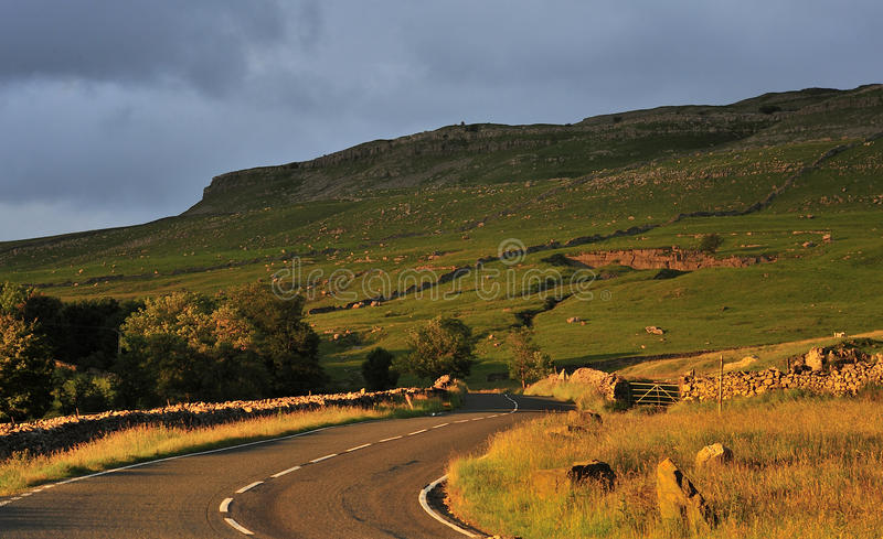 Yorkshire country road, sunset. Late evening sun illuminates this empty, rural roadway, the B6255,with Ingleborough common in the shadows. This scenic road stock photography