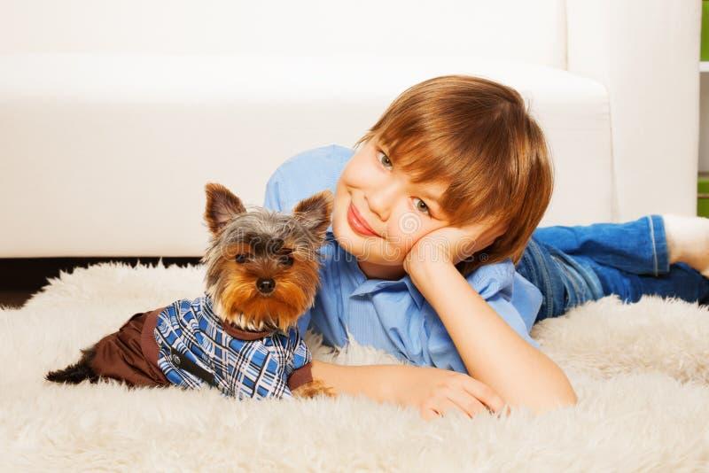 Yorkshire Terrier dans le pull avec le garçon sur le tapis images stock