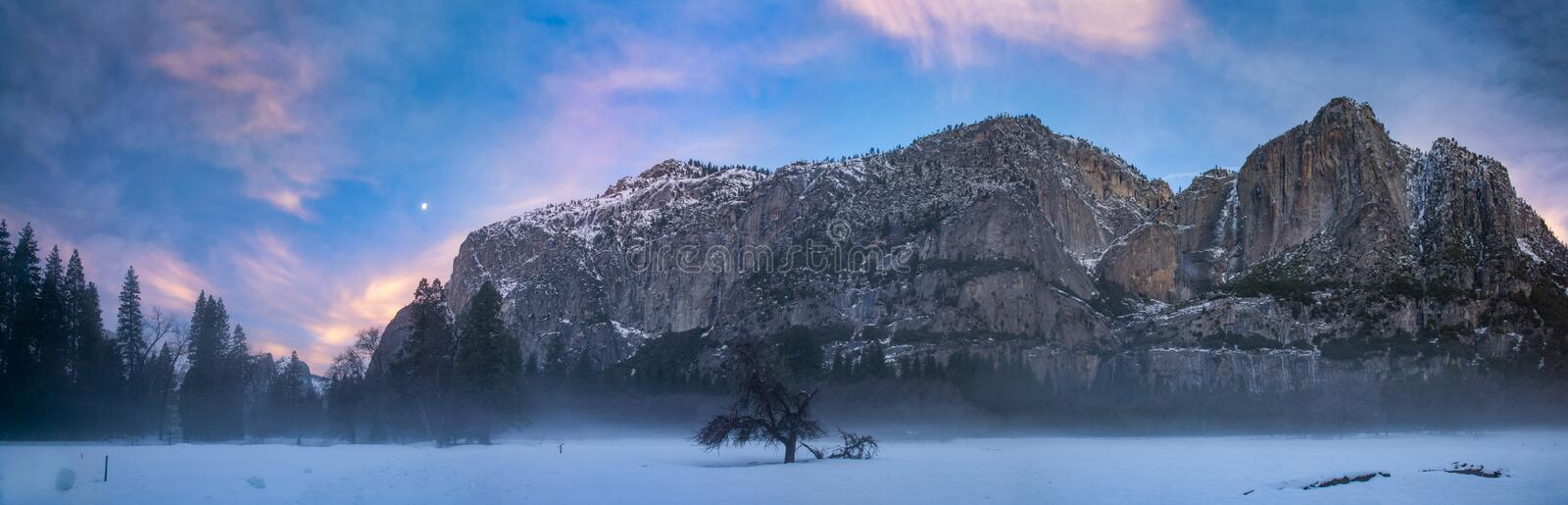 Yosemite at dawn with moon, clouds and thin fog. This is a photograph of foggy morning at Yosemite with colorful clouds and moon stock photography