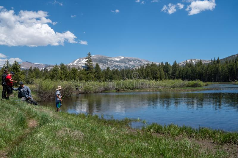 Yosemite National Park, CA - Family fishes in a small pond in Yosemite National Park, off of Tioga Pass on a sunny stock photo