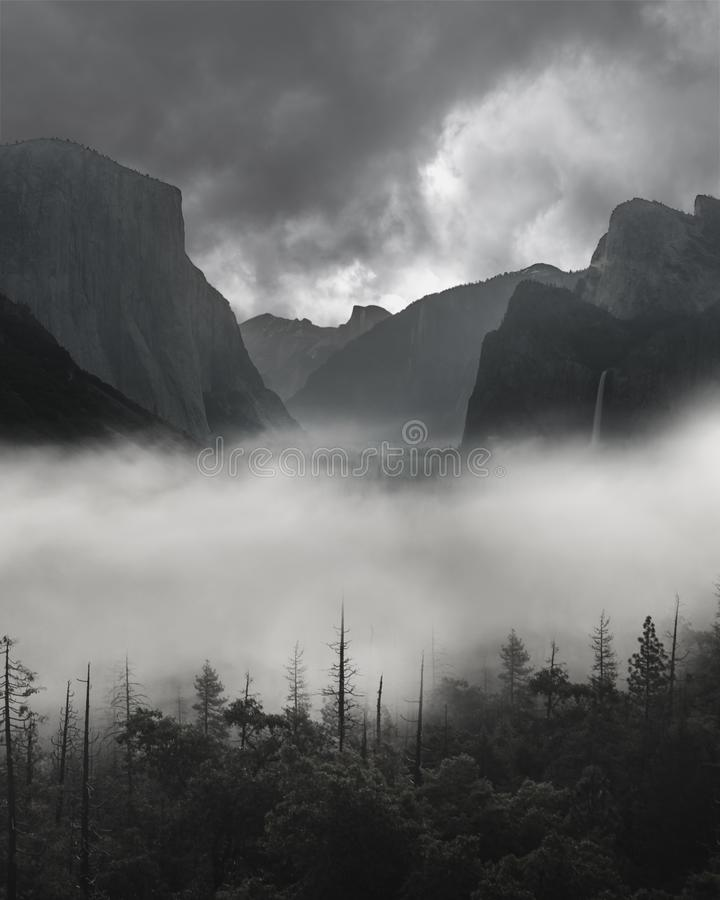 Photo of Black and White Yosemite Tunnel View Obscured by Heavy Fog with Stormy Dark Grey Clouds Approaching royalty free stock images