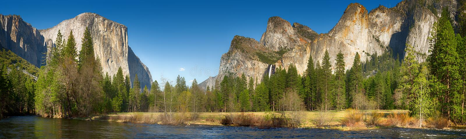 Yosemite valley and merced river. Yosemite Valley panorama showing the upper Yosemite Falls and the Bridalveil Falls with the Merced river in the foreground stock photo