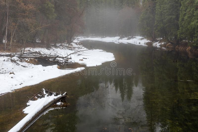 Yosemite in winter with the Merced river flowing calmly through a snowy forest stock photo