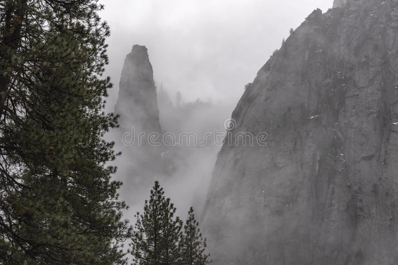 Yosemite in winter with mist hanging around the mountain sides royalty free stock photos