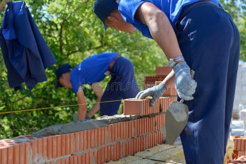 Construction mason worker bricklayer installing red brick. Yoshkar-Ola, Russia - June 2015 Construction mason worker bricklayer installing red brick with trowel royalty free stock photos