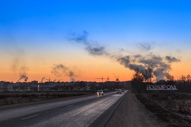 Yoshkar-Ola, Russian Federation - 11/24/2014: Winter highway at the entrance to the Yoshkar-Ola city.  Panoramic view of Yoshkar-O. La city at sunset. Twilight stock photo