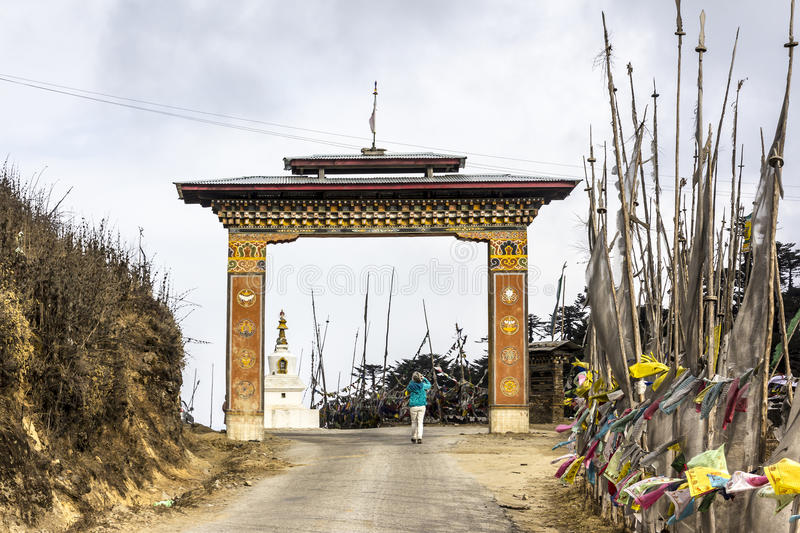 Yotong La pass. A tourist is taking a photograph of the gate and prayer flags at Yotong La pass at a height of 3300 m. Bhutan. In the background is a choerten. ( royalty free stock photos