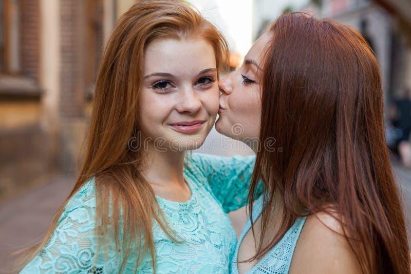 """You're我的最佳的friend† 两女孩亲吻 都市bac 库存照片"