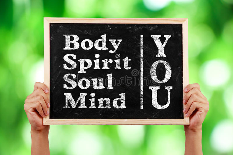 You Body Spirit Soul Mind. Hands holding blackboard with text You Body Spirit Soul Mind against green blurred background stock photography