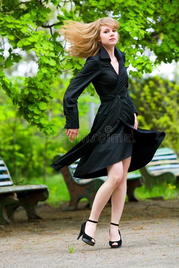 You can fly. Young slim girl with flying hair in the park royalty free stock image