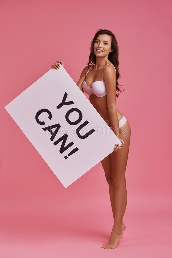 You can! Full length of attractive young woman holding a poster royalty free stock photos
