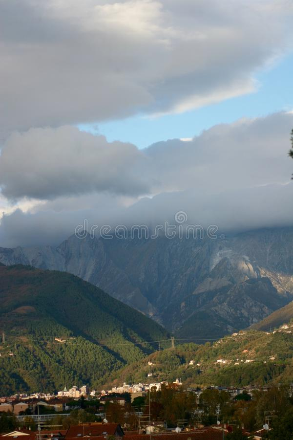 View of the mountains. You can see the sunlight shining on the mountains. the clouds hanging above. A nice view stock image
