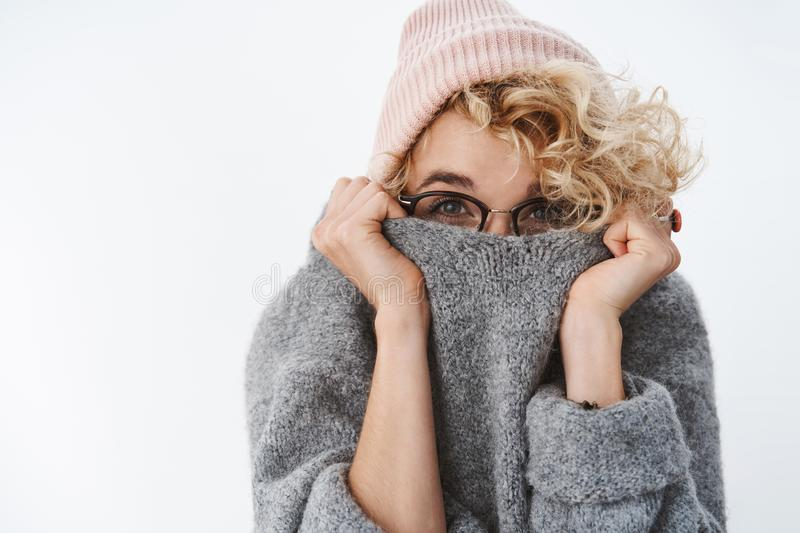 You cannot get me winter. Cute silly and playful blond girl in glasses and beanie pulling collar of sweater on face royalty free stock images