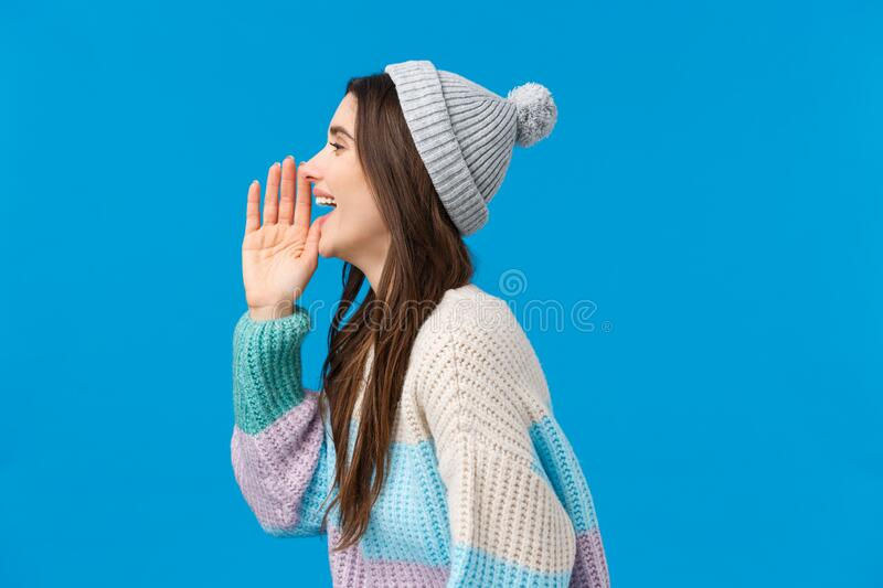 Are you coming or not. Happy and carefree outgoing smiling brunette girl in trendy winter sweater, hat, turn left and. Holding hand near opened mouth, calling royalty free stock photos