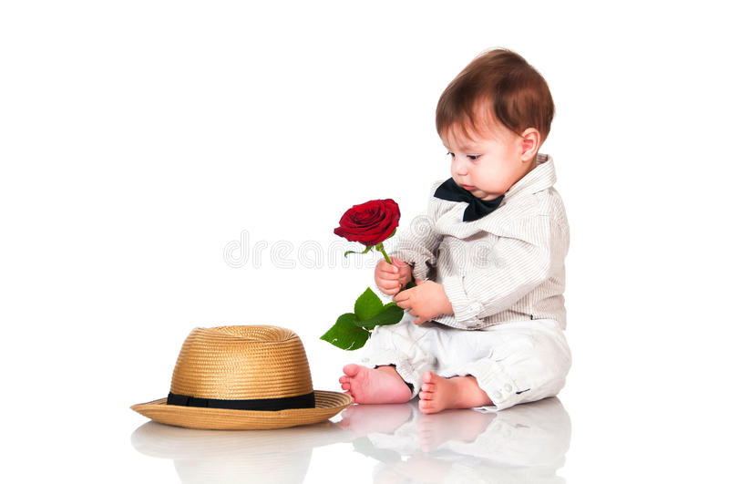 Little one old year boy with hat and red rose sitting on white background. Retro, vintage royalty free stock photography