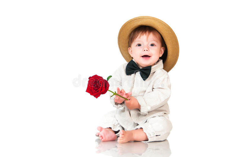 Smiling one old year boy in retro, bow-tie hat and with red rose sitting on white background. royalty free stock photos