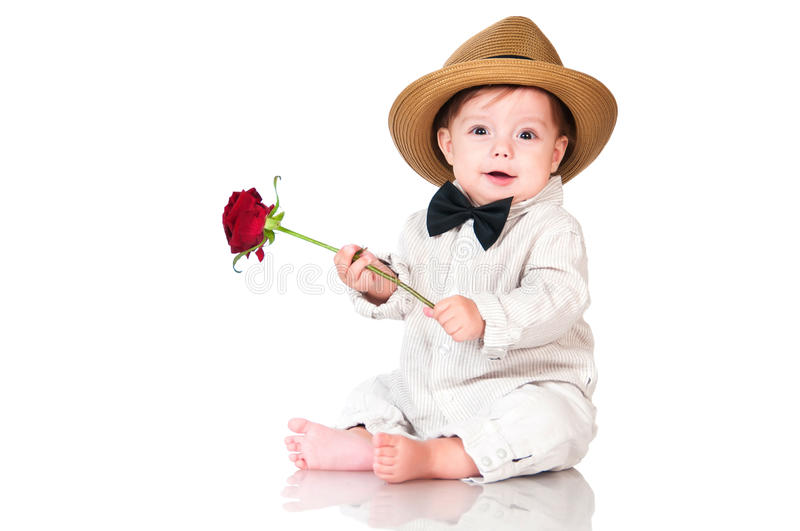 Smiling one old year boy in retro, bow-tie hat and with red rose sitting on white background. stock photos