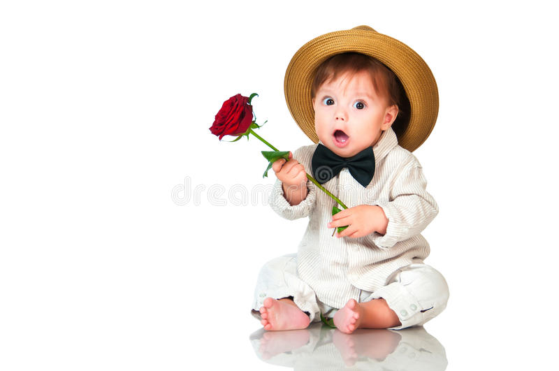 Emotional surprised toddler boy in retro, bow-tie hat and with red rose on white background. royalty free stock image