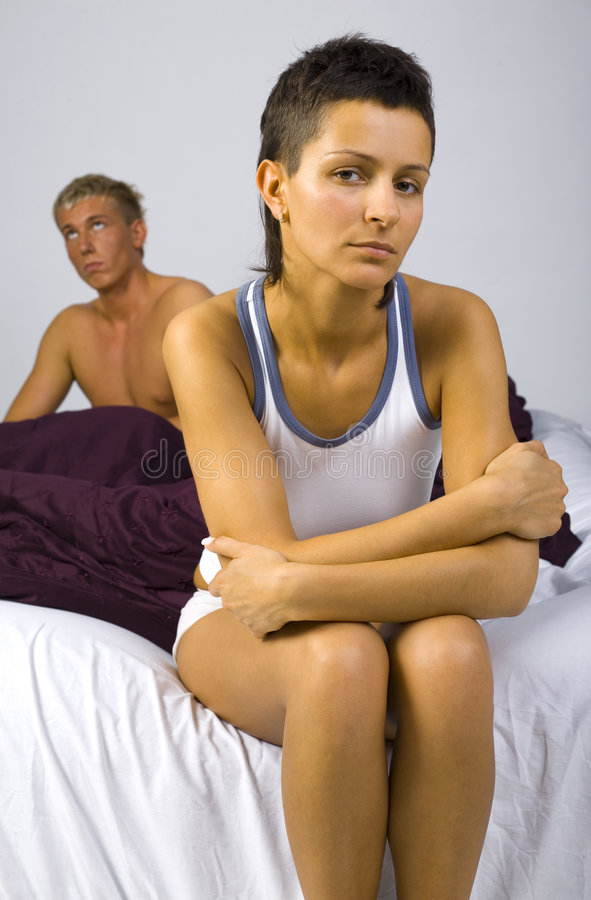 You didn't make it... Young sad woman sitting on bed, nearby unsatisfied man. Woman looking at camera. Gray background, front view stock images