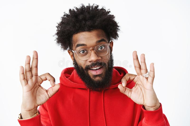 You doing great. Satisfied and delighted outgoing african american bearded man in glasses with afro hairstyle wearing. Red hoodie showing okay gesture in royalty free stock photos