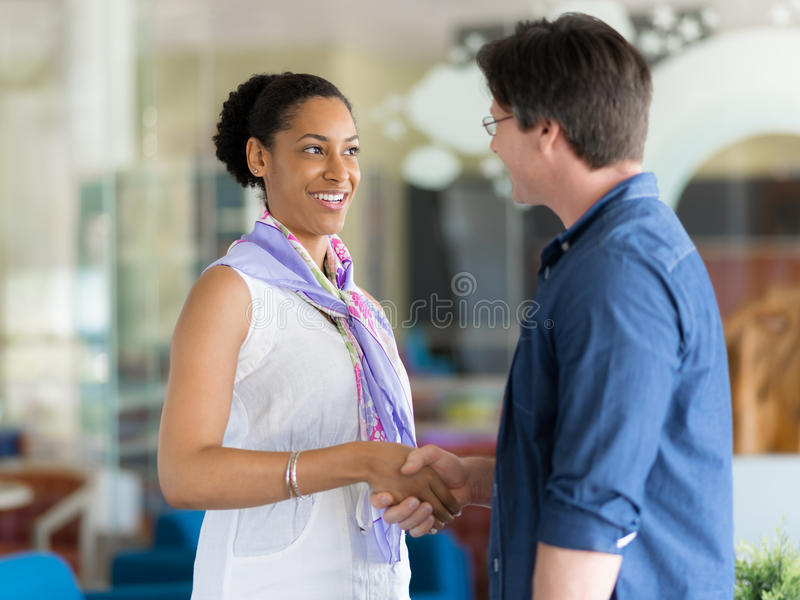 You are going to lov eit. Two young professionals shaking hands stock image