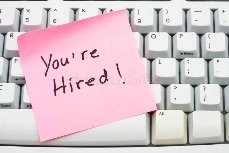 You are hired. A pink sticky note saying your hired sitting on a computer keyboard, computer note stock photography