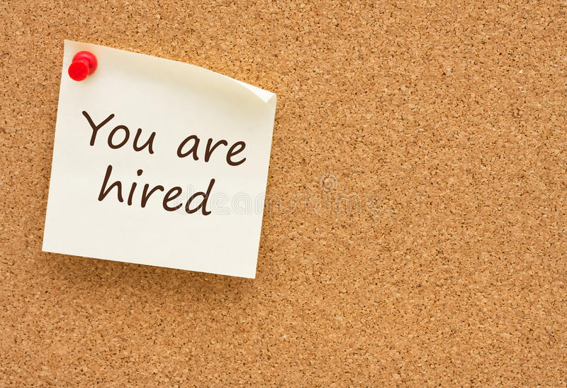 You are hired. A yellow sticky note on a corkboard, You are hired stock photography