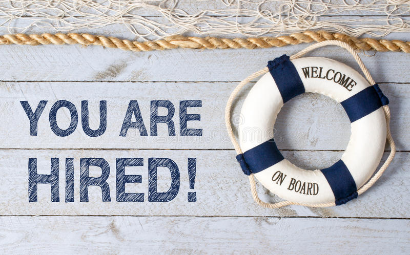 You are hired. In grunge blue block text on weathered wooden boards with rope, fishing net and life ring with text welcome on board stock image