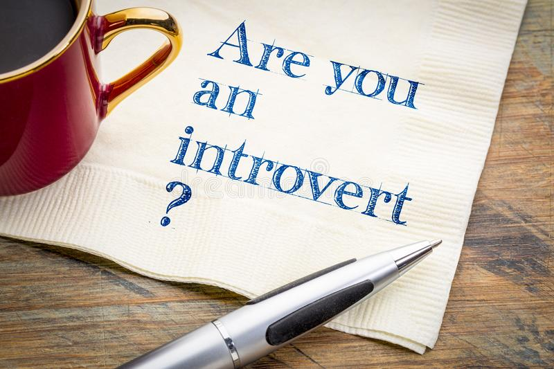 Are you an introvert?. Handwriting on a napkin with a cup of coffee stock image