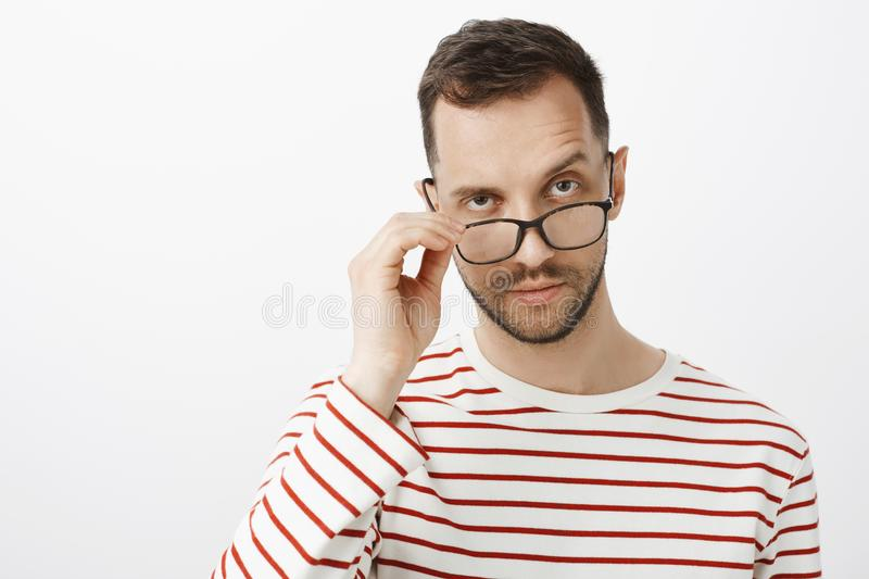 Are you joking with me. Indoor shot of doubtful serious adult enterpreneur with bristle, taking off glasses and lifting royalty free stock image