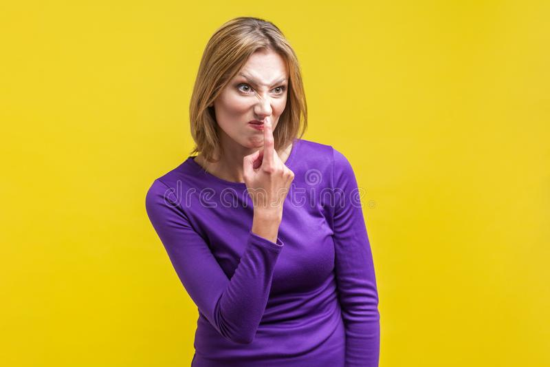 You lie! Portrait of angry young woman pointing at her nose. indoor studio shot isolated on yellow background stock photos