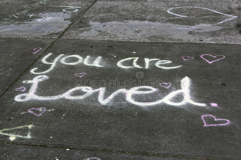 You are loved. A message you are loved was drawn with chalk on a pedestrian walkway stock photo