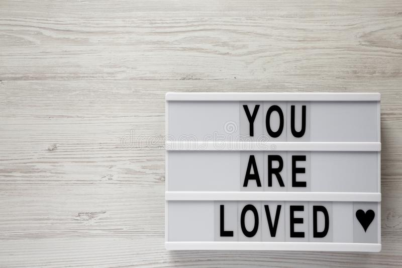 `You are loved` words on lightbox on a white wooden surface, top view. Flat lay, overhead, from above. Copy space. `You are loved` words on lightbox on a white stock photos