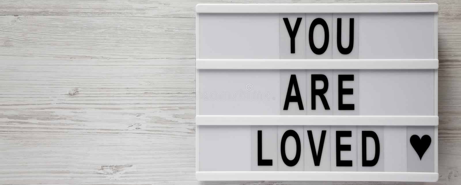 `You are loved` words on modern board on a white wooden background, top view. Flat lay, overhead. Copy space.  stock photo