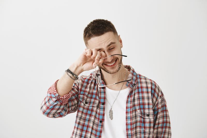 You made me laugh to tears. Happy good-looking unshaved male holding glasses while rubbing eyes, smiling while talking. With colleague over gray background. Guy royalty free stock image