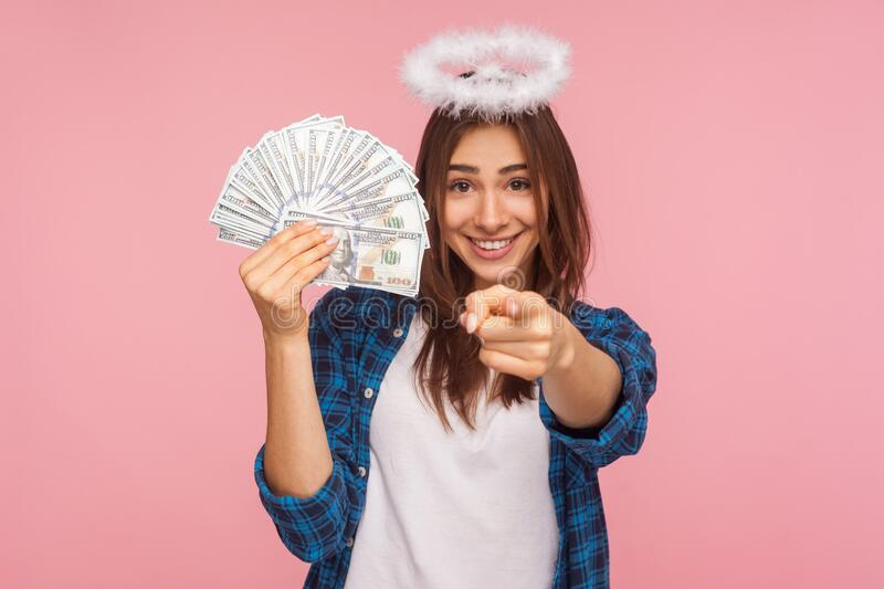 You may become rich! Portrait of happy lucky angelic girl with halo over head holding money and pointing to camera. Showing dollar bills, motivating to wealthy royalty free stock photography