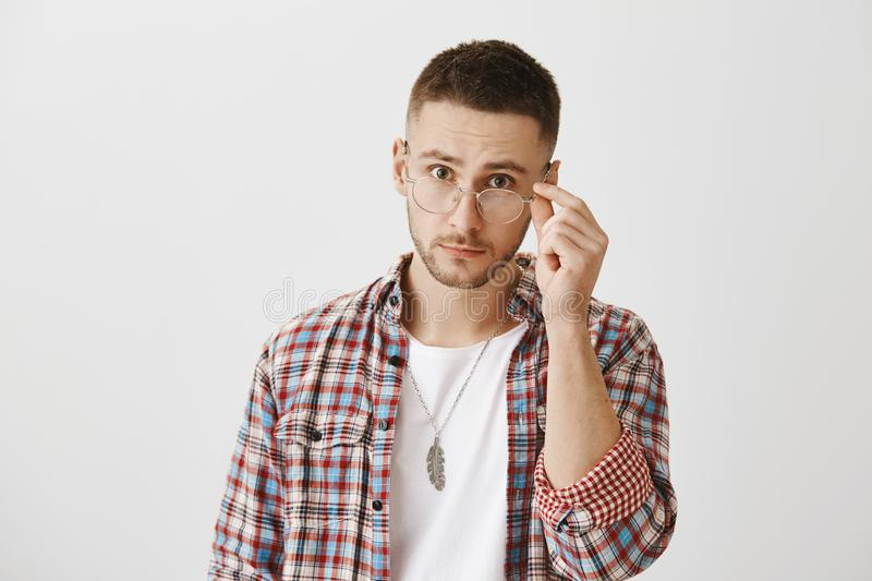 You really mean what you said. Surprised or questioned attractive student taking off trendy glasses and looking at royalty free stock images
