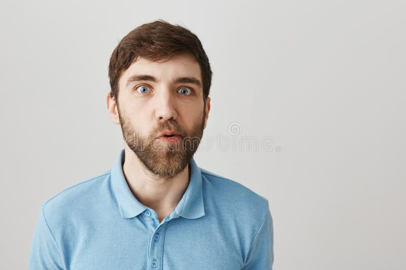 You must be joking. Portrait of confused cute bearded guy, standing with doubtful and questioned expression, moving jaw. And looking with popped eyes at camera royalty free stock image
