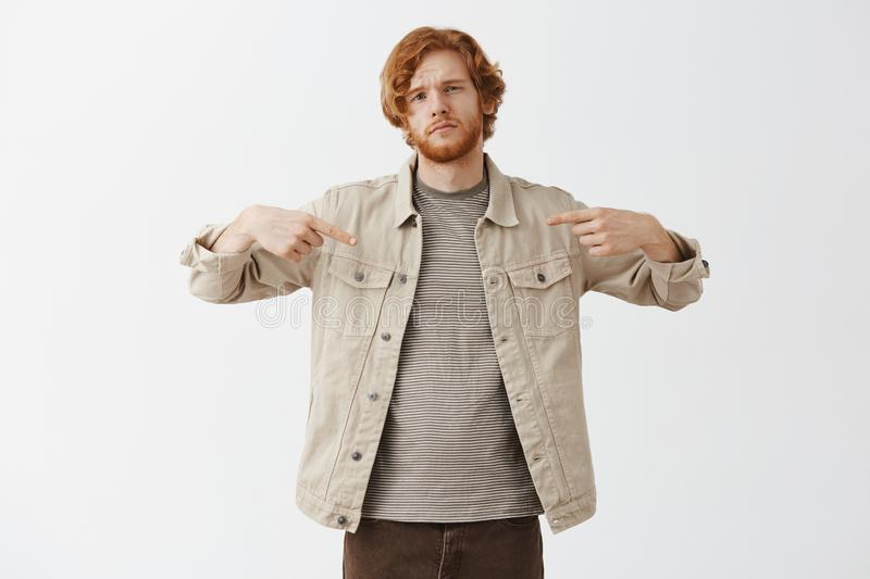 You need me. Cool and confident attractive redhead artistic guy in beige jacket over striped t-shirt pointing at himself stock photography