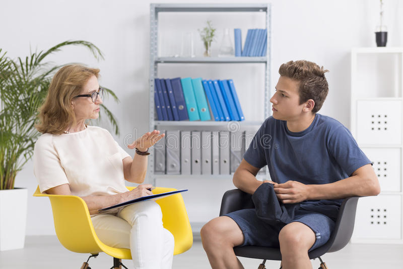 You need to change. Professional psychotherapist and her teenage patient, light interior royalty free stock images