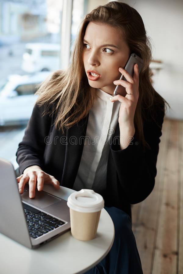 You never guess what I found online. Horizontal portrait of serious worried european woman sitting in cafe, drinking stock photography