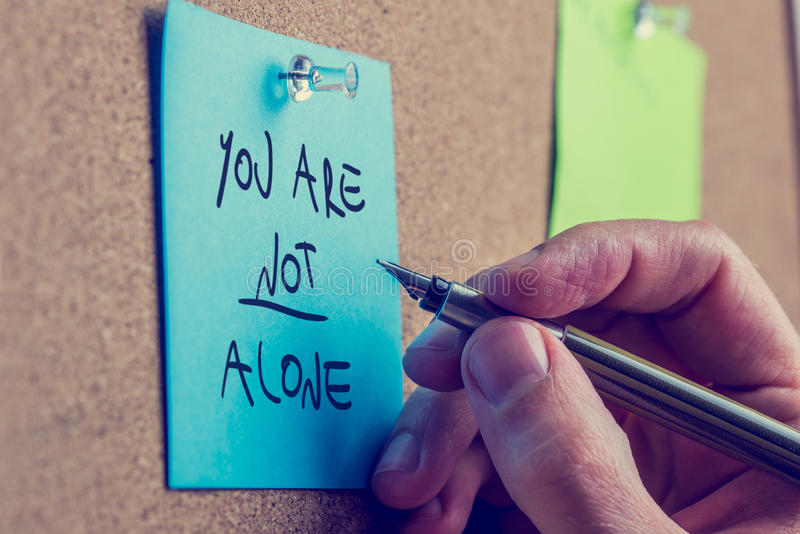You Are Not Alone. Man writing an inspirational message on a blue sticky note pinned to a cork board with a fountain pen stock photos