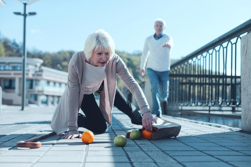 Scared woman dropping groceries while falling to ground. Are you ok. Selective focus on a scared senior lady standing on her knee and trying to pick up her stock image