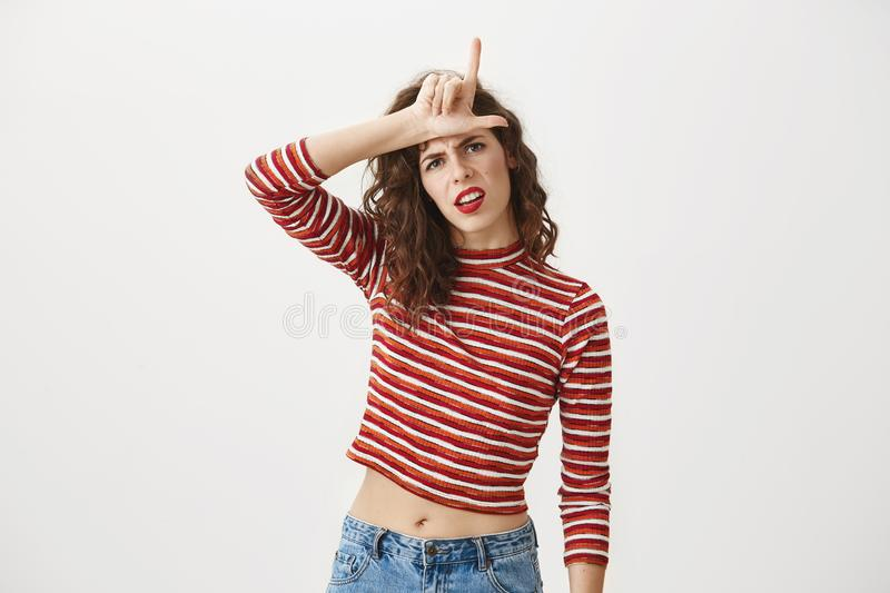 You are outsider. Studio shot of annoyed good-looking woman, feeling cool and confident while tilting head and showing. Loser-sign over forehead, standing with royalty free stock photography