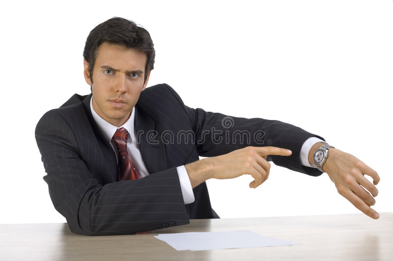 You'r late. Angry, handsome businessman. Seating behind desk, showing his watch. White background, front royalty free stock image